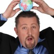 Businessman balancing a globe on his head — Stock Photo