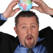 Stock Photo: Businessmbalancing globe on his head