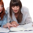 Young women looking up a word in the dictionary — Stock Photo
