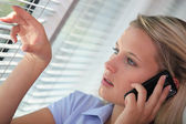 Woman on the phone looking through venetian blinds — Stock Photo