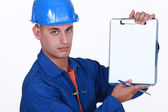 Tradesman holding up a blank clipboard — Stock Photo