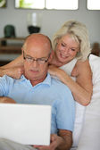 Senior couple sat on the sofa surfing the internet — Stock Photo