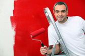 A man painting a wall red — Stock Photo