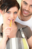 Woman biting piece of carrot — Stock Photo
