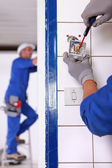 An electrician fixing an outlet. — Stock Photo