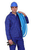 Man carrying coil of piping — Stock Photo