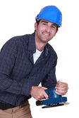 Workman with an electric sander — Stock Photo