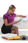 Blond businesswoman sat on a sofa reading through document — Stock Photo