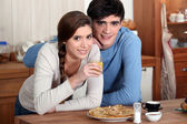 Young couple in kitchen eating pancakes — Stock Photo