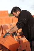 Mason making adjustments to brick — Stock Photo