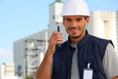 Construction worker speaking into his walkie-talkie — Stock Photo