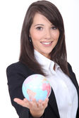 Portrait of a young woman holding a globe — Stock Photo