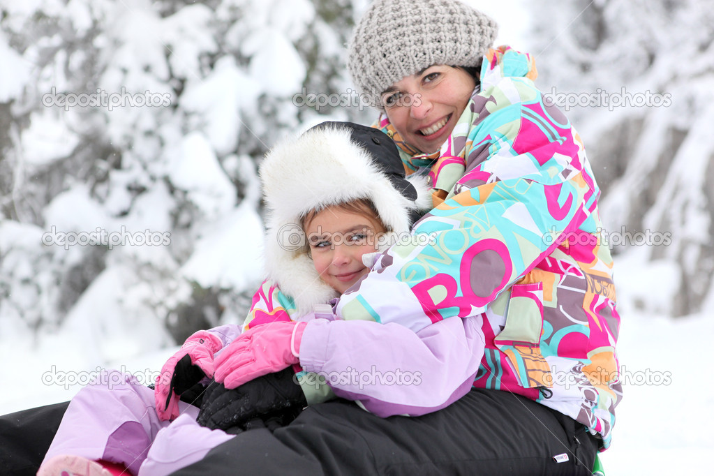 Mother and daughter playing in the snow together  Stock Photo #9613728