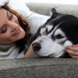 Young woman cuddling her dog — Stock Photo