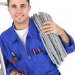Stock Photo: Worker carrying cabling coiled around his shoulder