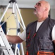 Bald manual worker stood with ladder — Stok fotoğraf
