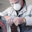Dusty man changing the paper on an electric sander — Stockfoto