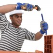 Bricklayer with a hammer and chisel - Stock Photo