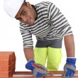 Mixed-race bricklayer taking measurements on brick wall - Stock Photo
