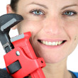 Royalty-Free Stock Photo: Close-up shot of a woman holding a pipe wrench
