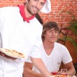 Smiling pizzaiolo serving customers — Stockfoto #9671675