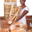 Young woman with a basket of baguettes in a baker's shop — Stock Photo