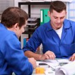 Foto Stock: Skilled tradesmen examining blueprint