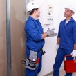 Electricians in front of electrical panel — Stock Photo #9672241