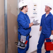 Stock Photo: Electricians in front of electrical panel