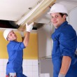 Electricians installing neon lights in ceiling — Stock Photo #9672272