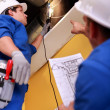 Stock Photo: Two workers inspecting ventilation system
