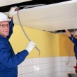 Two electricians working on false ceiling — Stock Photo