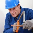 A tradesman using a saw to cut a copper tube — Stockfoto
