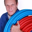 Electrician with rolls of blue and red corrugated plastic tubing — Stock Photo #9673416