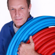 Electrician with rolls of blue and red corrugated plastic tubing - Stock Photo