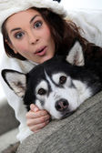 Woman with a dog on the sofa — Stock Photo