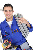 Worker carrying cabling coiled around his shoulder — Stock Photo