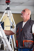 Bald manual worker stood with ladder — Stock Photo