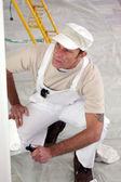 Painter kneeling to inspect work — Stock Photo