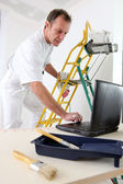 Painter taking quick break to reply to e-mail — Stock Photo