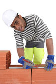 Mixed-race bricklayer taking measurements on brick wall — Stock Photo