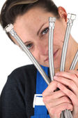 Female plumber holding selection of metal pipes — Stock Photo