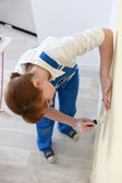Woman smoothing a wallpaper seam — Foto Stock