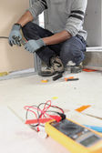 Electrician kneeling by voltmeter — Stock Photo