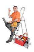 Labourer sat on ladder holding laptop computer — Stock Photo