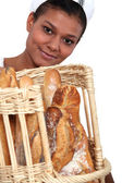 Bakery worker holding basket of bread — Stock Photo