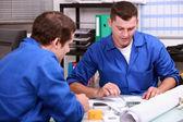 Qualifizierte handwerker, die prüfung einer blaupause — Stockfoto