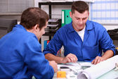 Skilled tradesmen examining a blueprint — Stock Photo