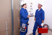 Electricians in front of electrical panel — Stock Photo