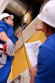 Two workers inspecting ventilation system — Stockfoto